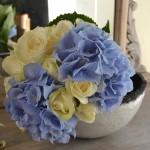 Bouquet clásico de rosas blancas abiertas y cerradas y hortensias azules.