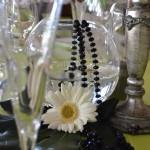 Detalle de decoración con pecera de cristal, gerbera blanca y candelabro antigüo y collar negro.