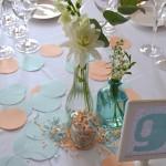 Decoración de mesa con flor blanca y confeti en azul y melocotón.