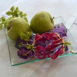 Centro de mesa con base de cristal compuesto por manzanas, gelatina morada, flor de alchemilla y gloriosa.
