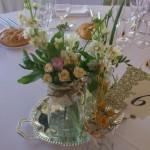 Decoración sobre bandeja de plata con botes rústicos con flor silvestre.