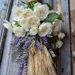 Atado rústico de espigas de trigo, flor de lavanda y rosa ramificada blanca.