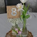 Rústica decoración con fresias, tulipanes y paniculata y nunmeración en tela.