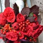 Ramo de rosas inglesas rojas, cala negra, hoja granate de avellano y frutos de viburnum.